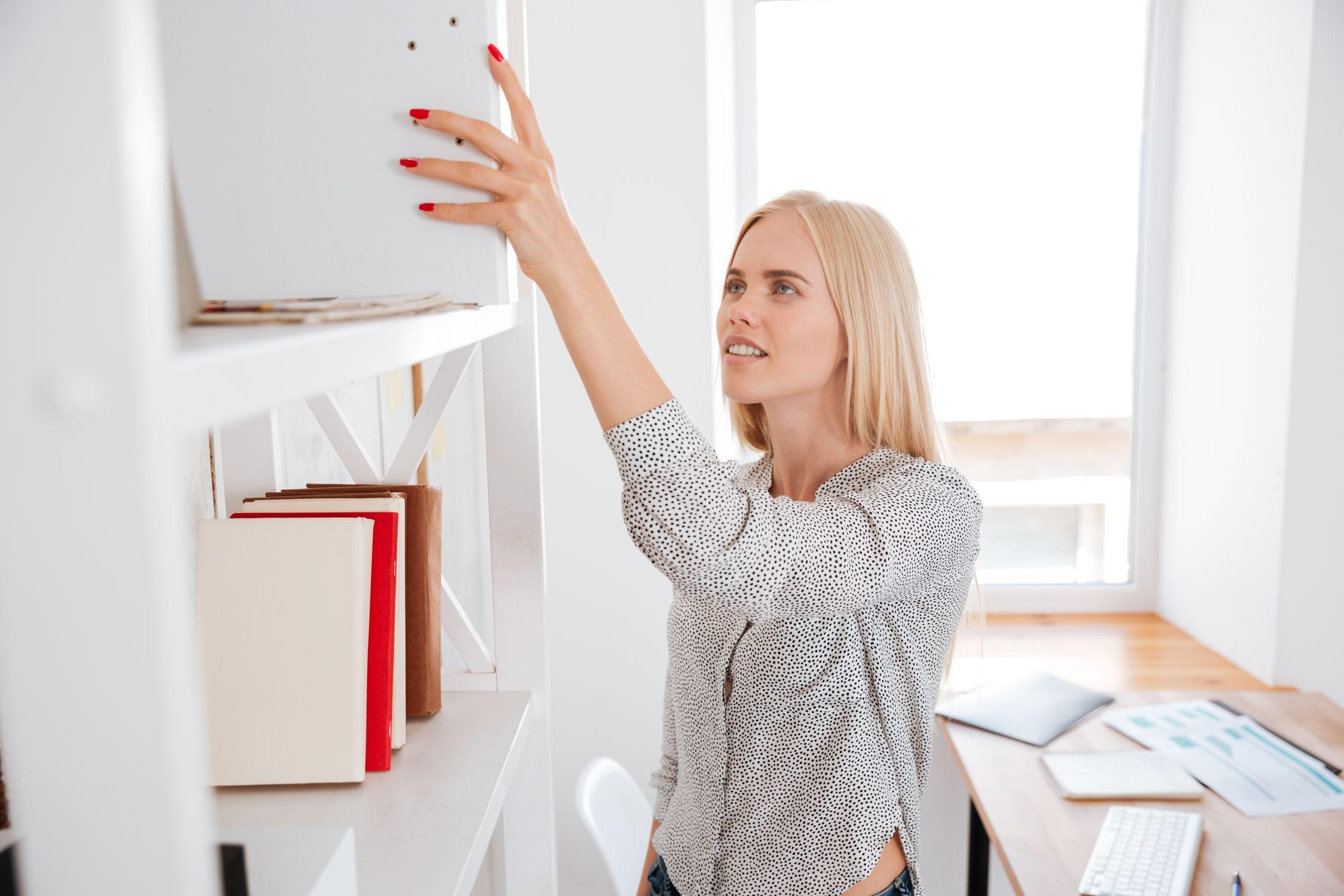 Businesswoman taking book from a shelf while standing in office
